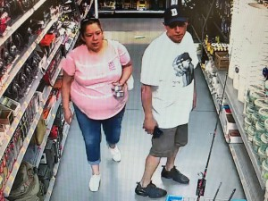 A man and woman standing next to each other. The woman wearing a pink top and cropped jean capris is walking next to a man in white shirt and khaki shorts on CCTV.